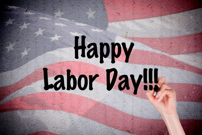Hand writing Happy Labor Day on grunge wall with American flag